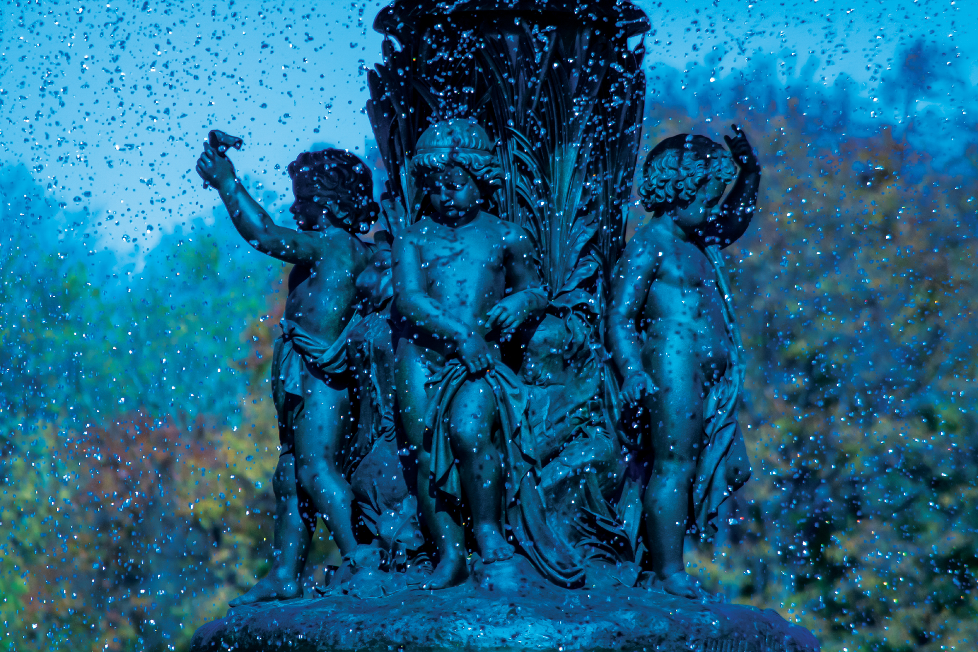Blue tinted photograph of cherub babies from Bethesda fountain in central park. Taken in the fall in Manhattan, New York