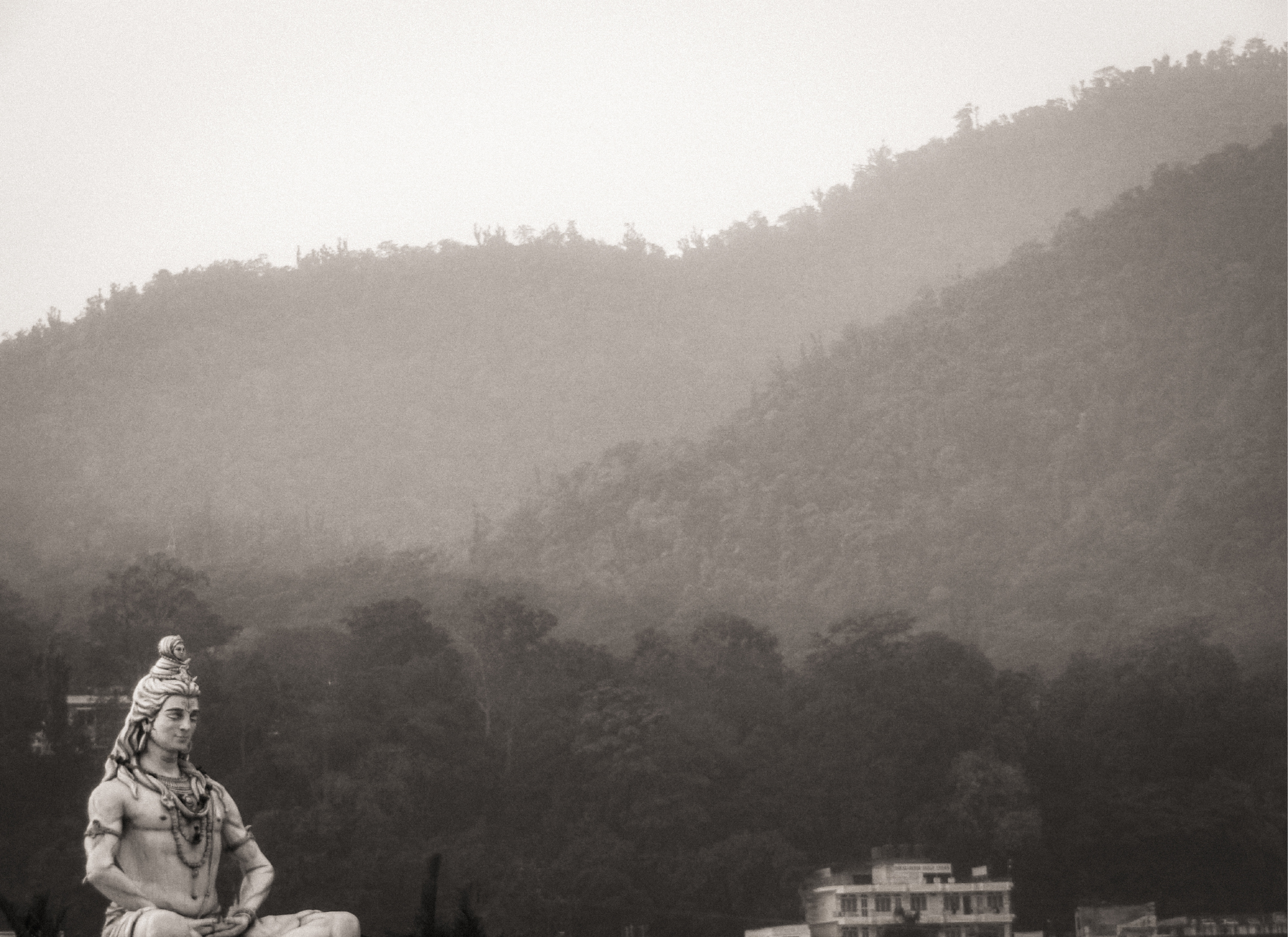 Black and white photograph of a Shiva Statue with tall mountains in the background. Taken in Rishikesh, India