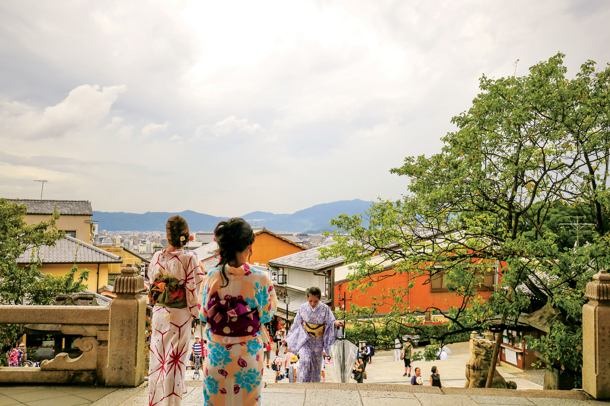 Colorful photograph of women dressed up in kimonos overlooking Kyoto downtown, Mountains can be seen in the distance