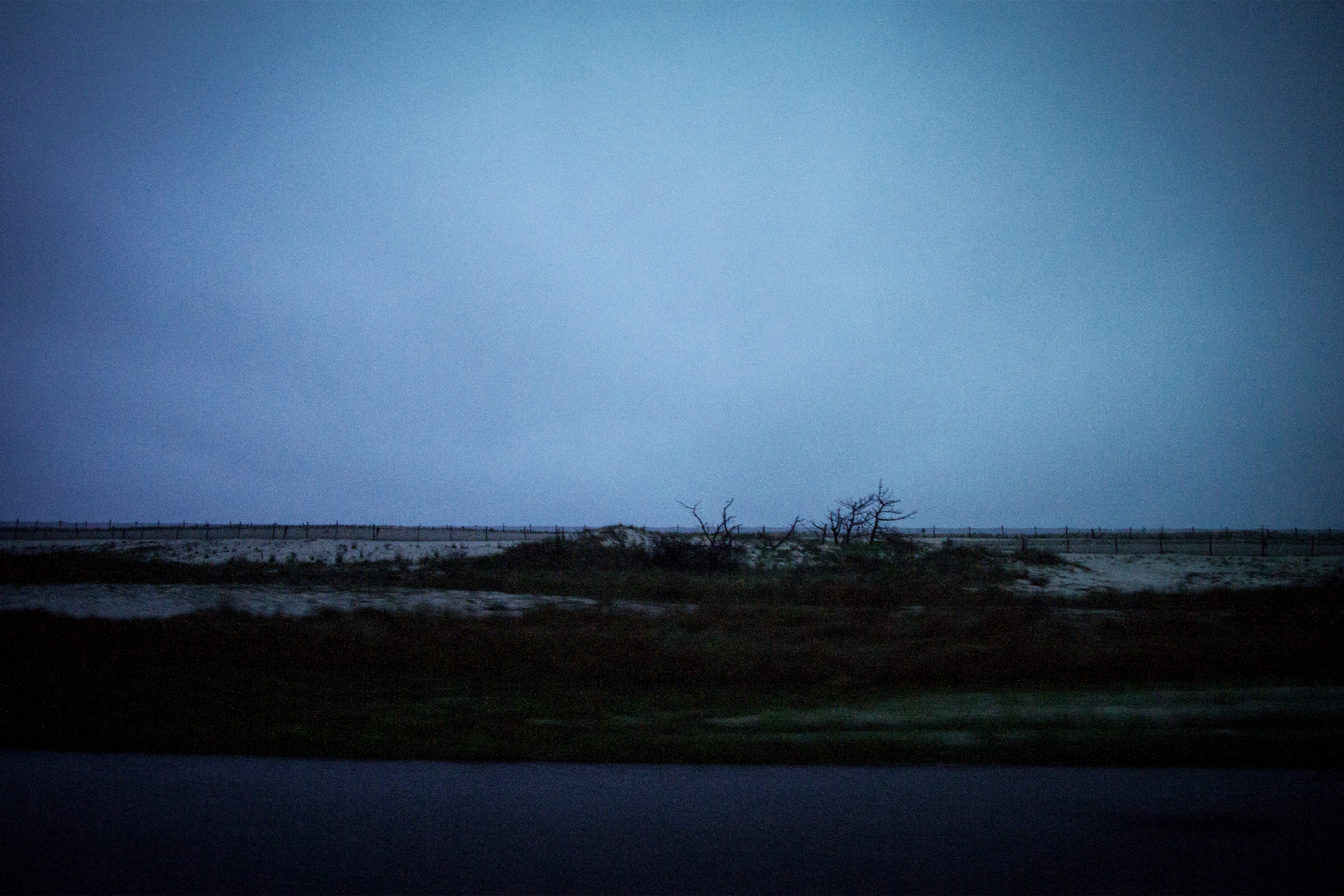 Photograph of vast open sky taken in the evening in the winter while in Maryland. Some beach can be seen.