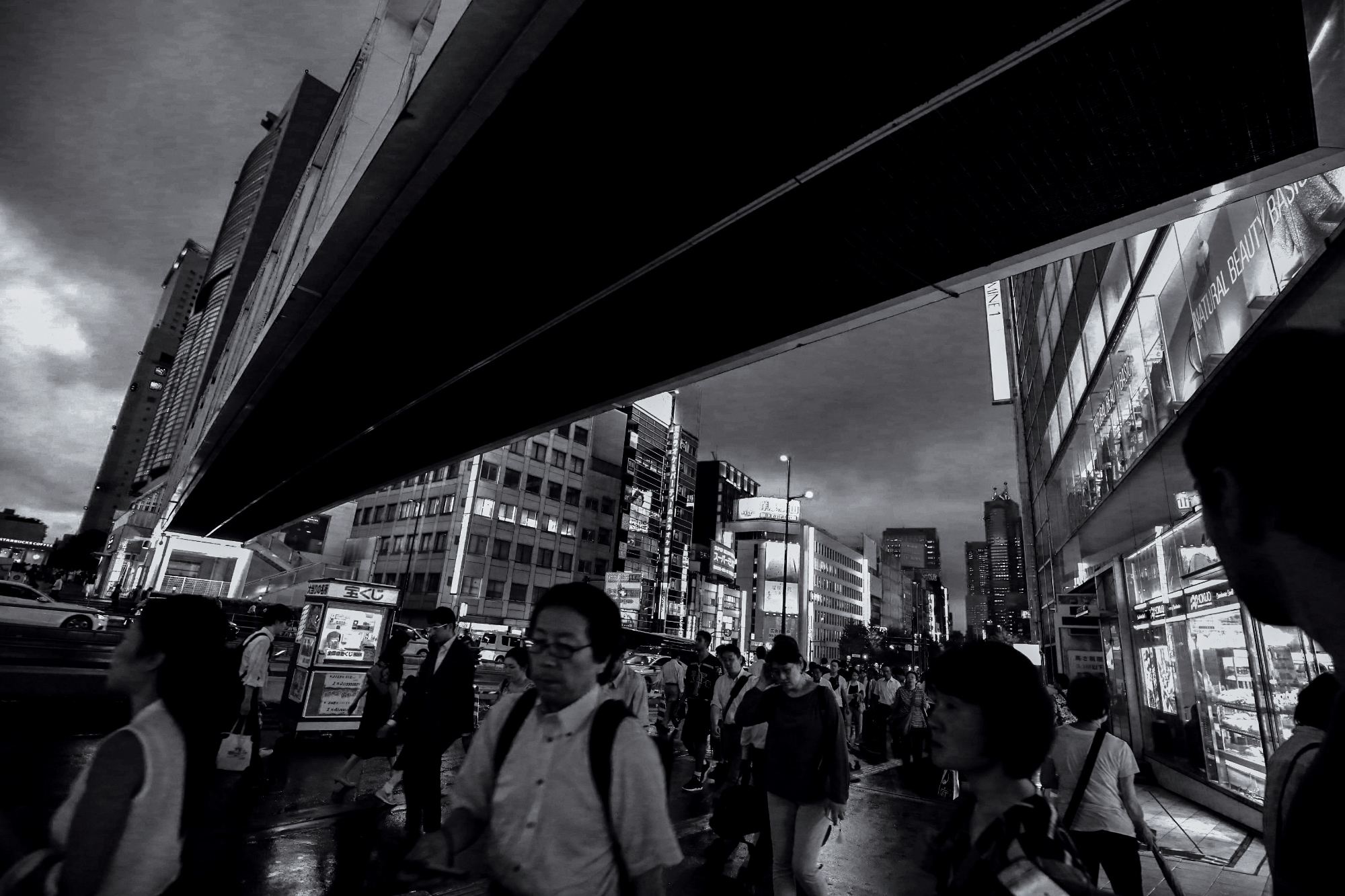 Black and white photograph of people rushing down the busy city streets of Tokyo, Japan