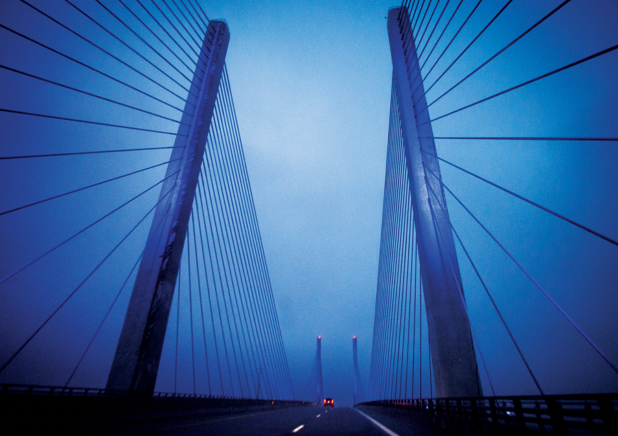 Photograph of a bright blue bridge with prominent suspension chords taken in Maryland.