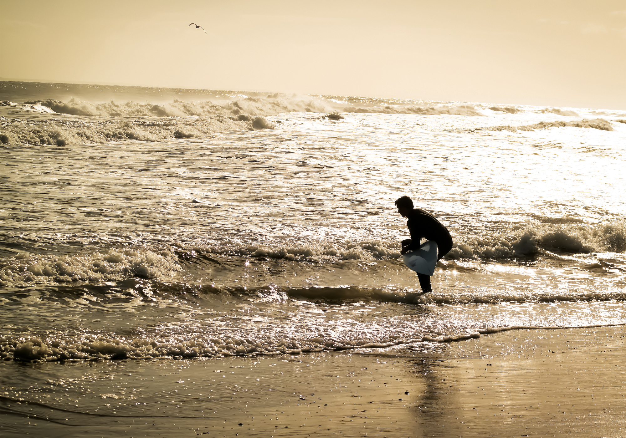 Photograph of a surfer getting ready to walk into the water at sunrise on the beach.