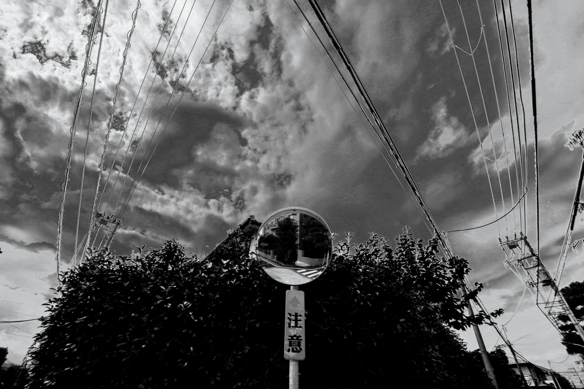 Black and white, symmetrical image with leading lines. The sky is cloudy, the focus is on a mirror reflecting the street below. Taken in Tokyo, Japan