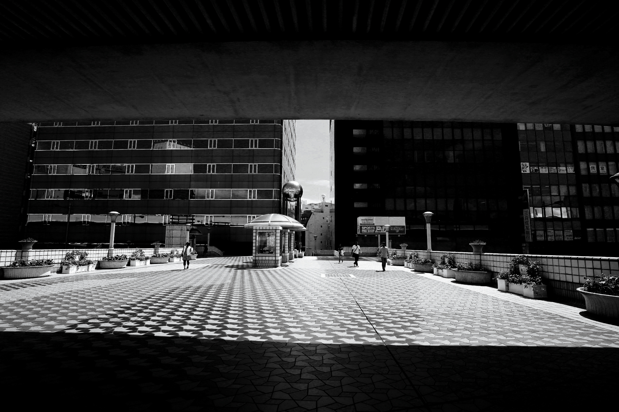 Black and white photograph of a scene filled with symmetrical lines and architecture. Taken in Tokyo, Japan