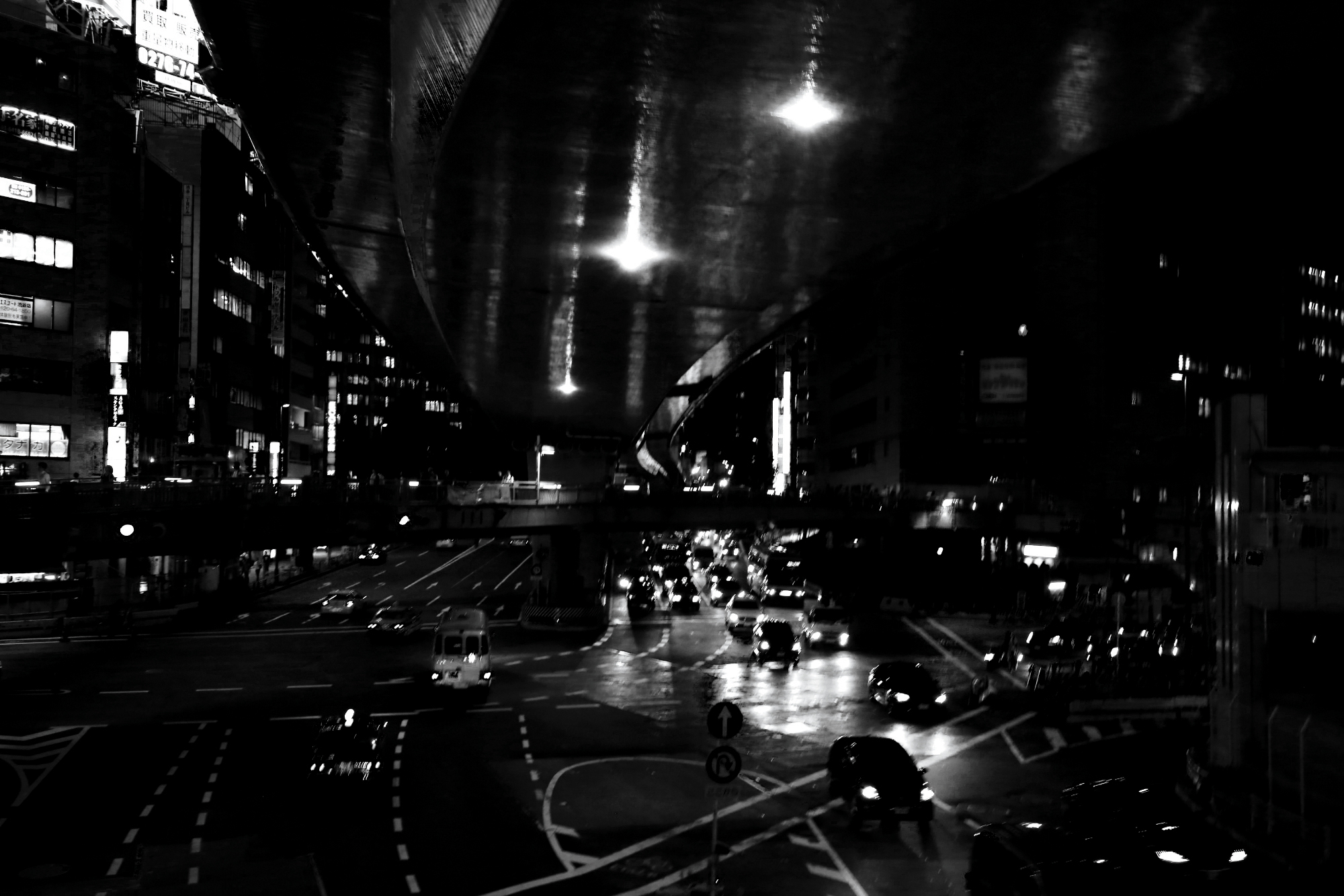 Timeless, black and white, moody, image of a street with cars driving down it at night. Taken in Tokyo, Japan