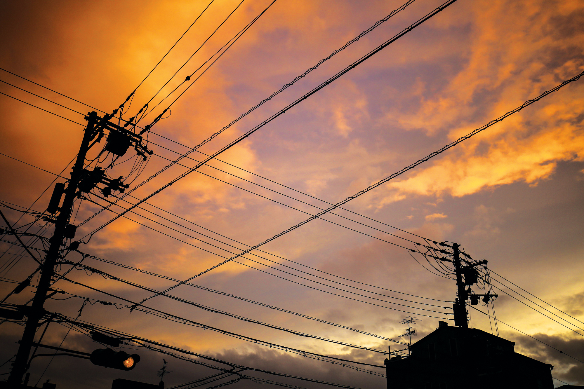 Beautiful, soft, image taken of a sky at sunset with symmetrical street wires under it. Taken in Kyoto, Japan