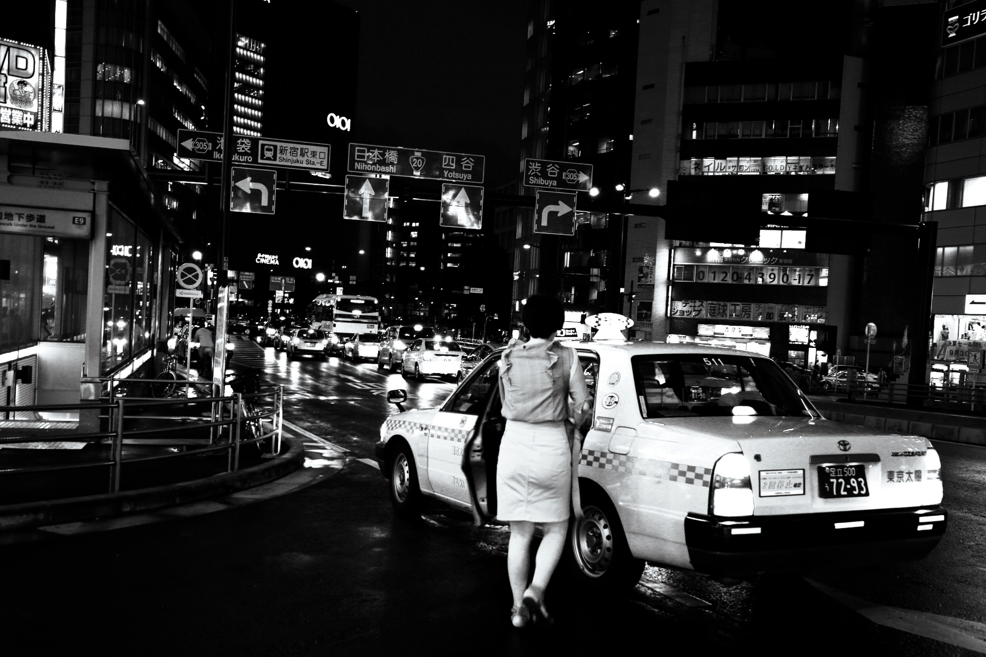 Black and white photograph of a woman stepping into a taxi, taken in Tokyo, Japan