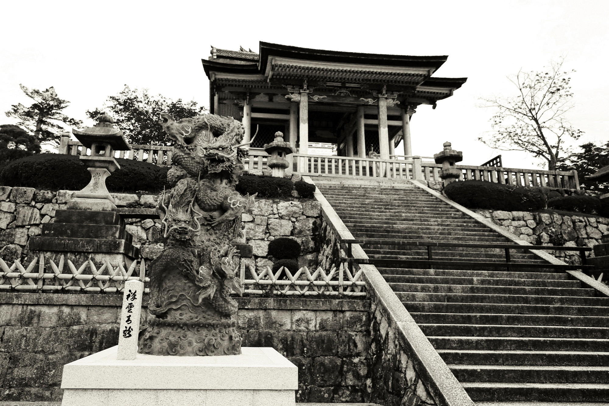 Photograph of a temple taken in Kyoto, Japan. Image looks very old, with sepia tones. There's a dragon statue in the front of a very old looking temple