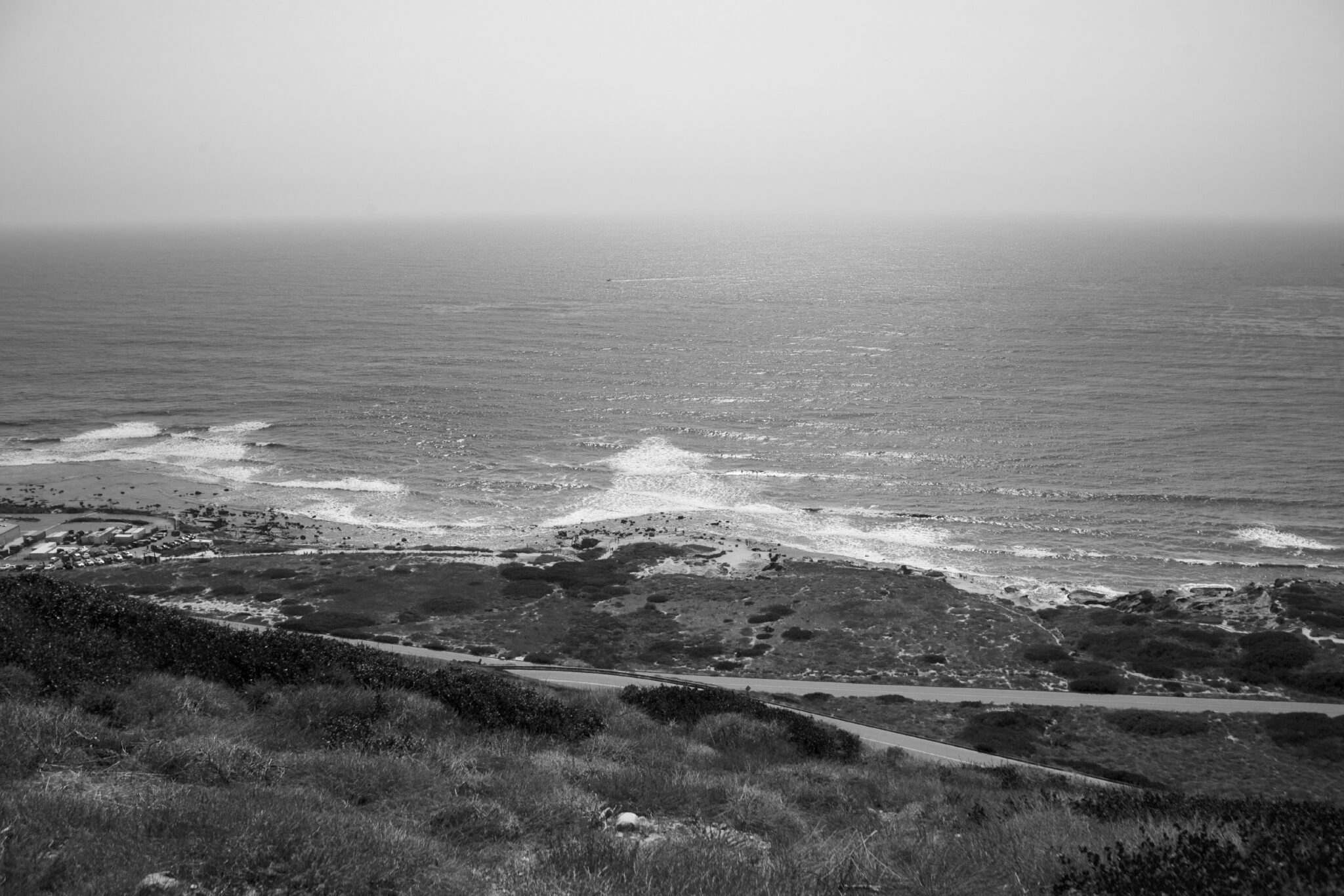 Stunning black and white image taken from the top of a mountain looking down to the ocean below and in the distance