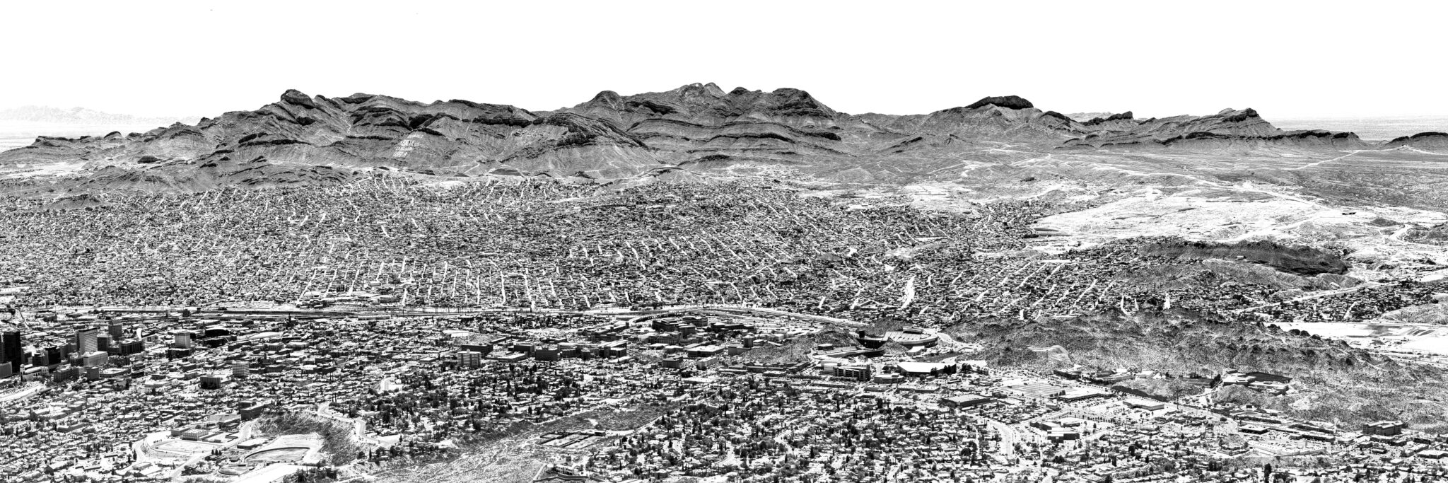 Black and white landscape photograph of the Franklin Mountains in El Paso, Texas. The mountains surround the city and can be seen for miles and miles.